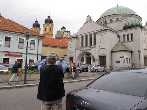 Trencin, Slovakia -- a man takes a picture of the former synagogue, with a church and the castle in the background
