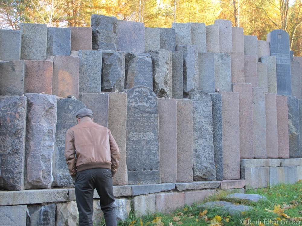 A man examines the memorial made from gravestones that had been used to build stairs