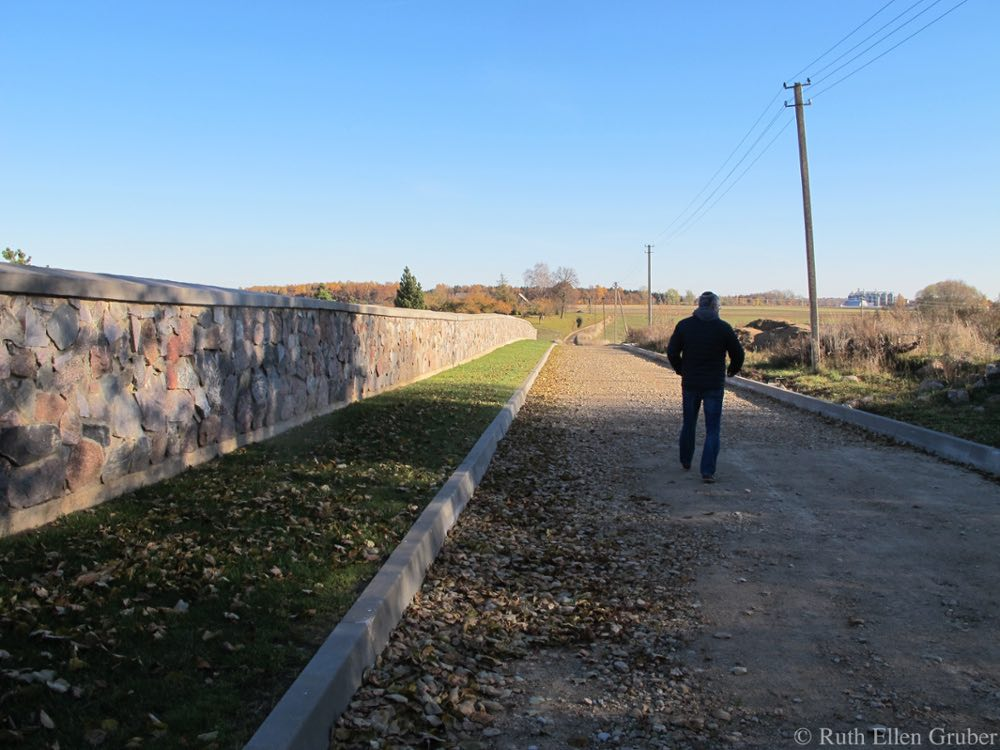 Sergey Kanovich walks along the wall of the restored Jewish cemetery at Seduva, Lithuania